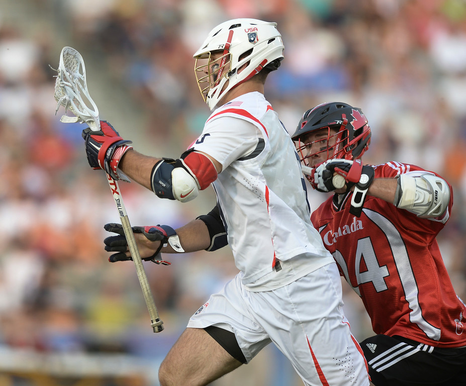 . COMMERCE CITY, CO - JULY 19: US attack Garrett Thul (9) carried the ball past Canada midfielder Jordan MacIntosh (24) in the first half. The United States faced Canada in the FIL World Lacrosse Championship game Saturday night, July 19, 2014.  Photo by Karl Gehring/The Denver Post