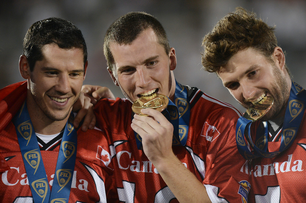 . COMMERCE CITY, CO - JULY 19:  Cameron Holding, center, bit into his gold medal as he and teammates posed for pictures after the game. Canada defeated the United States 8-5 in the FIL World Lacrosse Championship game Saturday night, July 19, 2014.  Photo by Karl Gehring/The Denver Post