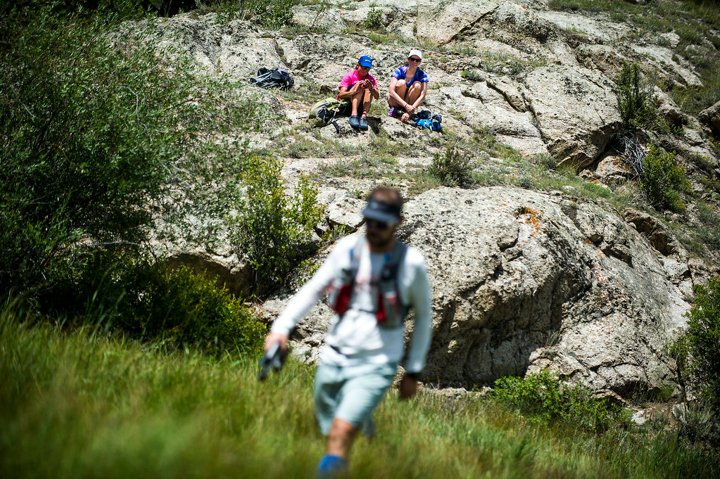 . Race spectators Annie Farris Murphy and Yitka Winn cheer on runners from a rock, as the runners make their way along the trail leading from downtown Twin Lakes during the 2014 Leadville Trail 100 ultramarathon on Saturday, August 16, 2014 in Twin Lakes, Colorado.  (Photo by Kent Nishimura/The Denver Post)