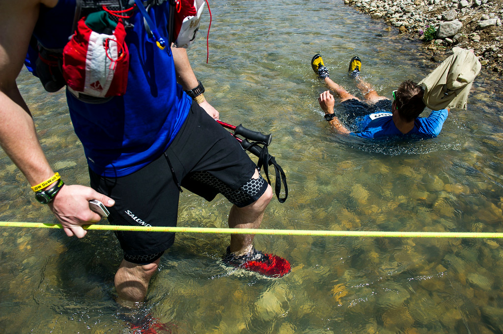 . Cory Harelson #300 lays down in the cold water of Lake Creek as other runners make their way across Lake Creek during the 2014 Leadville Trail 100 ultramarathon on Saturday, August 16, 2014 in Twin Lakes, Colorado.  (Photo by Kent Nishimura/The Denver Post)