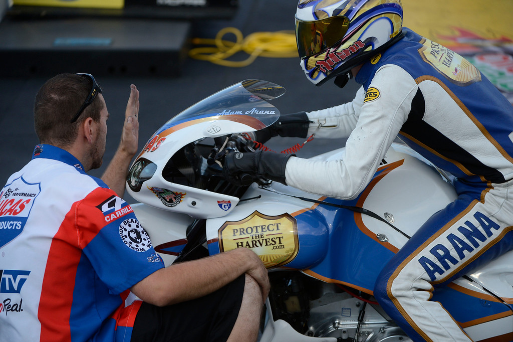 . MORRISON, CO - JULY 19:  NHRA pro stock motorcycle racer, Adam Arana, gets lined up by a crew member on the start line during qualifying at the Mopar Mile-High Nationals Friday evening at Bandimere Speedway, July 19, 2013.  (Photo By Andy Cross/The Denver Post)