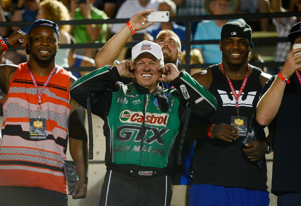 . MORRISON, CO. - JULY 18:  NHRA Funny Car driver, John Force, plugs his ears as he hung out with a ferw Denver Broncos near the start line to watch the few remaining Top Fuel drivers Friday evening, July 18, 2014 during the 2014 Mopar Mile High NHRA Nationals at Bandimere Speedway. (Photo By Andy Cross / The Denver Post)