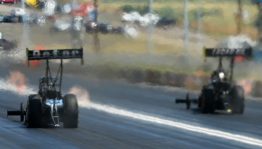 . Top Fuel cars head down the thrack during the Top Fuel competition at the MOPAR Mile High Nationals July 20, 2014 at Bandimere Speedway. (Photo by John Leyba/The Denver Post)