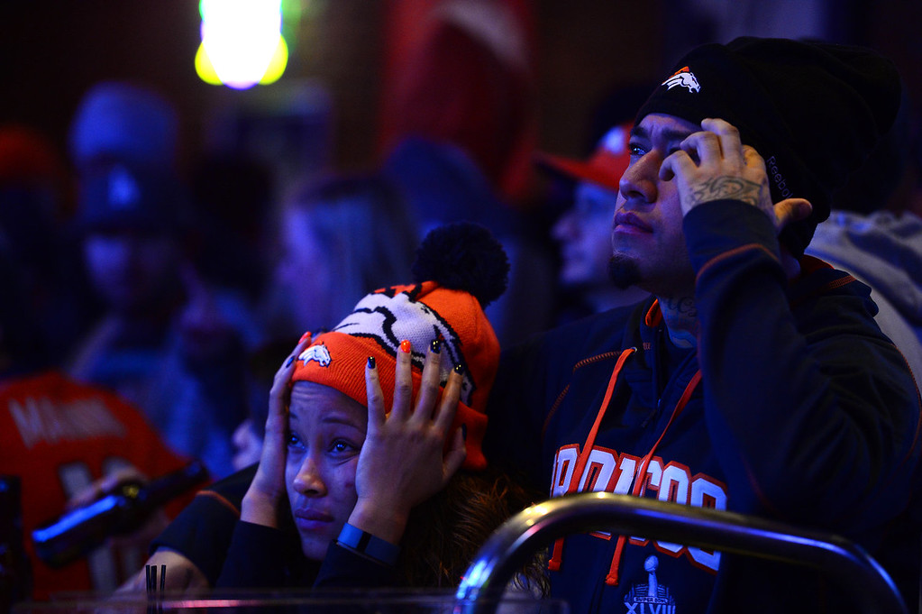 . Broncos fans Tatiana Bohorquez and Jorge Puerto can\'t believe their eyes as they watch the Seattle Seahawks score another touchdown during the second half of the Super Bowl while watching the game  at Jackson\'s bar in Denver, Co on February 2, 2014. The Broncos took on the Seattle Seahawks in Super Bowl XLVIII at the Met Life stadium in New Jersey. The Broncos lost to the Seattle Seahawks 43-8.  (Photo By Helen H. Richardson/ The Denver Post)