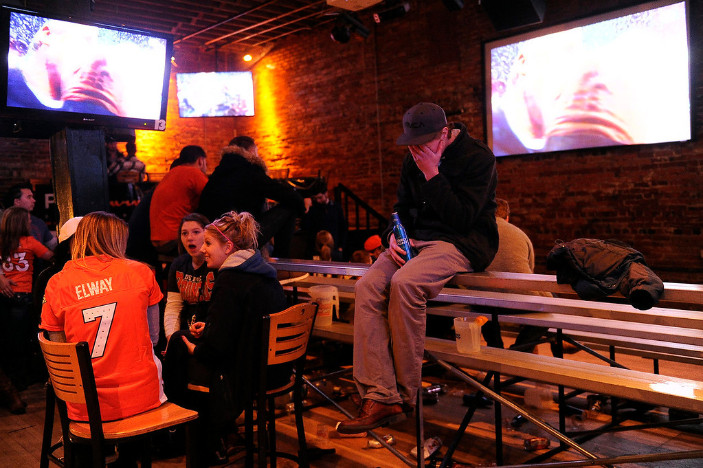 . EJ Russell, 23, sits alone at Jacksons Bar in Denver, Colorado following the Denver Broncos loss in Super Bowl XLVIII to the Seattle Seahawks 43-8 on February 2, 2014 (Photo by Seth McConnell/The Denver Post)