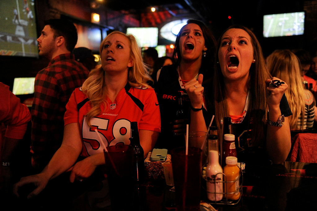 . Becky Roth, 22, right, lets out a frustrated yell during the closing minutes of the second quarter as Megan Noe, 24, left, and Maggie Roth, 24, look on during a  Super Bowl XLVIII watch party at Jackson\'s Bar in Denver, Colorado on February 2, 2014. (Photo by Seth McConnell/The Denver Post)