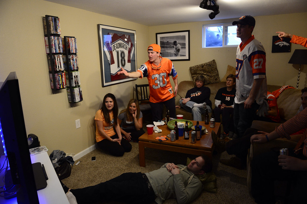 . Denver Broncos fans gather at the Denver home of Kevin O\'Connor, standing left, to watch the Broncos play in th Super Bowl. O\'Connor is gesturing at the TV in disbelief after the first play of the game resulted in a safety and two points for the Seattle Seahawks. (Kathryn Scott Osler, The Denver Post)