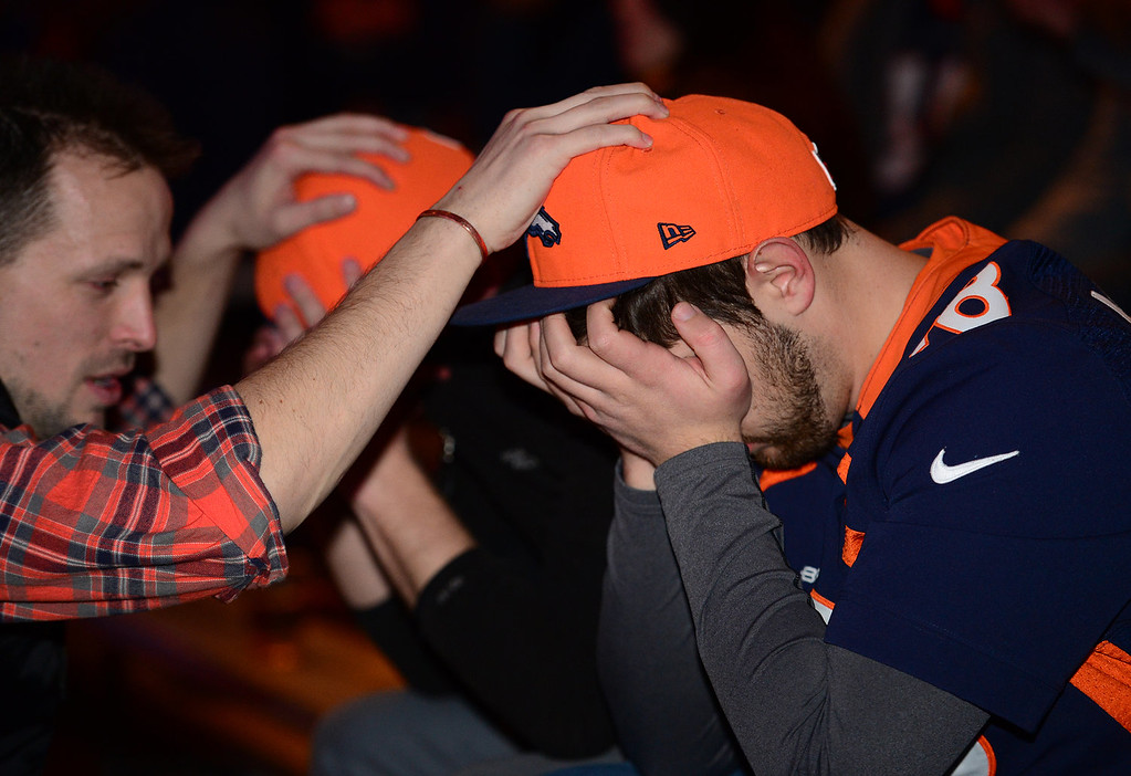 . Broncos fans Donald Fehlman, right, and Josh Duvall, get comforted by friend Cjad Stevens, left, as they hold their heads in their hands after the  Broncos loss to the Seahawks in the Super Bowl  at Jackson\'s bar in Denver, Co on February 2, 2014. The Broncos took on the Seattle Seahawks in Super Bowl XLVIII at the Met Life stadium in New Jersey. The Broncos lost to the Seattle Seahawks 43-8.  (Photo By Helen H. Richardson/ The Denver Post)