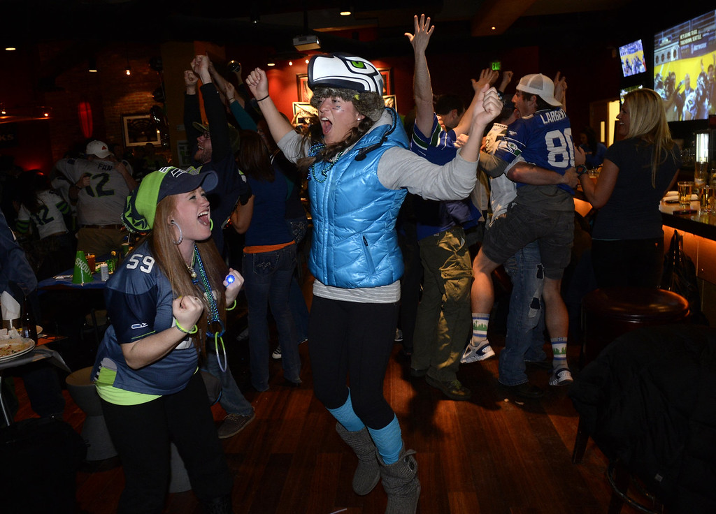 . Seattle Seahawks fans, Jessica Howard, left, and Melinee Fischer celebrate a Seahawk touchdown against the Denver Broncos during Super Bowl XLVIII Sunday evening, February 02, 2014 at Lucky Strike in the Pavillions in downtown Denver. (Photo by Andy Cross/The Denver Post)