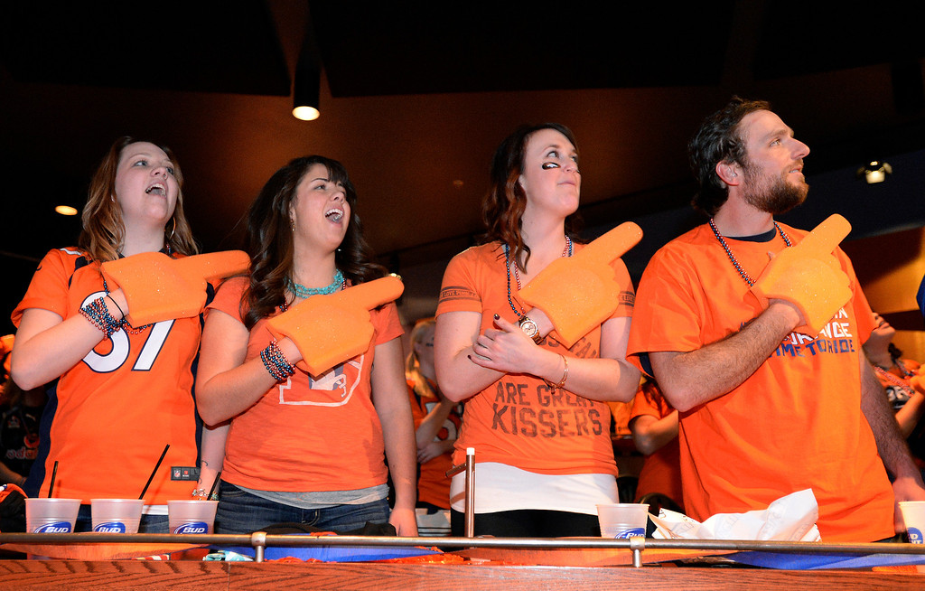 . Denver Broncos fans packed into The Soiled Dove Underground in Denver for the Super Bowl party on Sunday, February 2, 2014. As Renée Fleming sang the national anthem, Broncos fans left to right: Macy Wareham, Kimberly Sabo, Katie Hite and Bill Sulze hold their foam fingers over their hearts.  (Denver Post Photo by Cyrus McCrimmon)