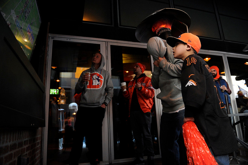 . Omar Gomez, 26, covers his head after a bad play by the Broncos during the first half as he cheers on the Broncos in Super Bowl XLVIIIat the Tilted Kilt in Denver, Colorado on February 2, 2014. (Photo by Seth McConnell/The Denver Post)