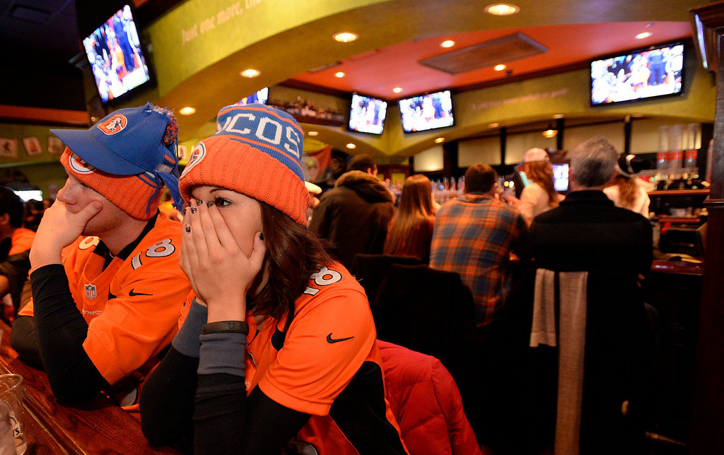 . Denver Broncos fans packed into Tilted Kilt in downtown for the Super Bowl party on Sunday, February 2, 2014. By the 4th quarter it was pretty ugly, as Tom Stoffel, left and Courtney McCombs can\'t bear to watch the ending. Denver lost 43-8.  (Denver Post Photo by Cyrus McCrimmon)