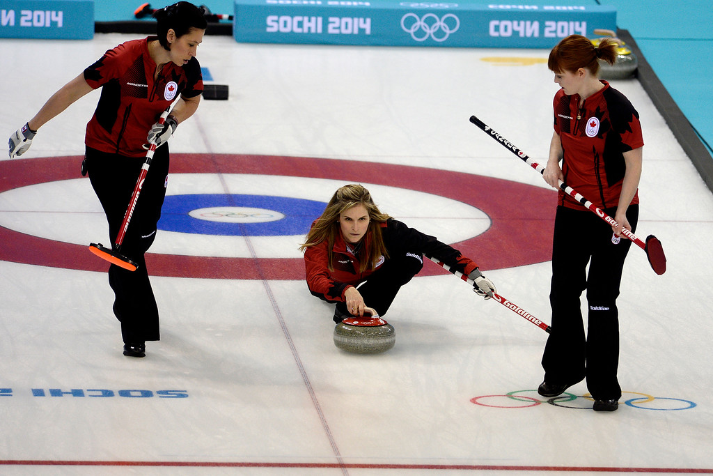 . Canadian curler Jennifer Jones throws the stone as sweepers Jill Officer (left) and Dawn McEwen look on during a women\'s curling qualifier against Great Britain at the Ice Cube Curling Center. (Photo by AAron Ontiveroz/The Denver Post)