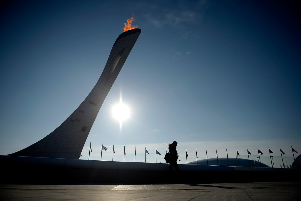 . A woman walks in front of the Olympic Torch during opening weekend at the Olympic village during the Sochi 2014 Winter Olympics on Saturday, February 8, 2014. (Photo by AAron Ontiveroz/The Denver Post)