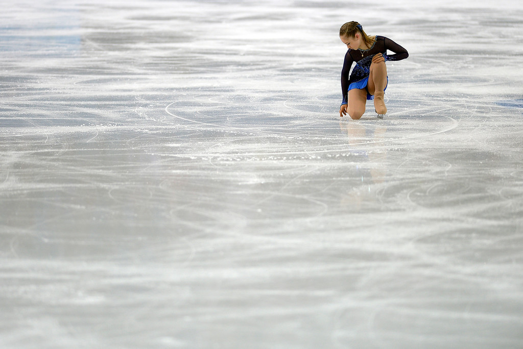 . Russia\'s Yulia Lipnitskaya runs her fingers across the ice en route to finishing first with a score of 72.90 in ladies short program during team figure skating on Saturday, February 8, 2014. (Photo by AAron Ontiveroz/The Denver Post)