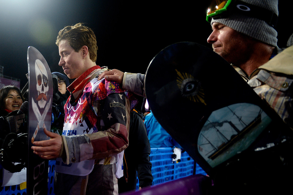 . Shaun White reacts as longtime trainer Bud Keene places a hand on his shoulder after the two-time defending gold medalist finished fourth in the men\'s snowboard halfpipe final on Tuesday, February 11, 2014. (Photo by AAron Ontiveroz/The Denver Post)