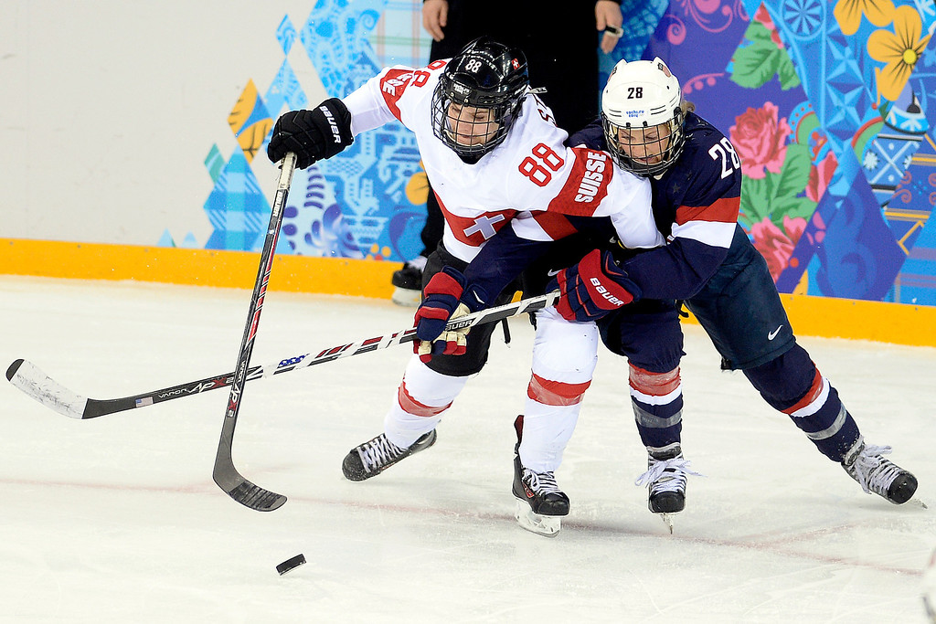 . Amanda Kessel (28) of the U.S.A. defends Phoebe Stanz (88) of the Switzerland during the third period of the United States\' 9-0 win at the Shayba Arena on Monday, February 10, 2014. (Photo by AAron Ontiveroz/The Denver Post)