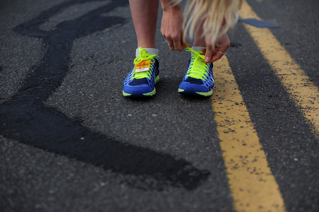 . A runner ties her shoes before the start of the 36th Annual BolderBOULDER 10K road race on Memorial Day, May 26, 2014. (Photo By Lindsay Pierce/The Denver Post)