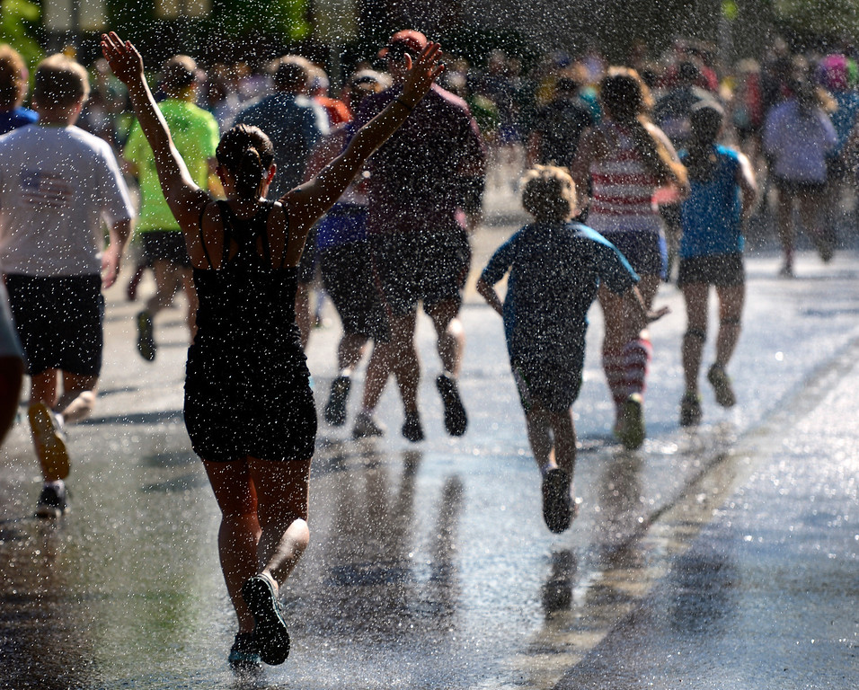 . With about a mile to go, runners get a cool mist of water as they make their way to Folsom Street. The 36th BolderBoulder takes place on the streets of Boulder, CO on Memorial Day, May 26, 2014. The 10K event brings winds through the streets of Boulder and finishes at Folsom Field on the University of Colorado campus. (Kathryn Scott Osler, The Denver Post)