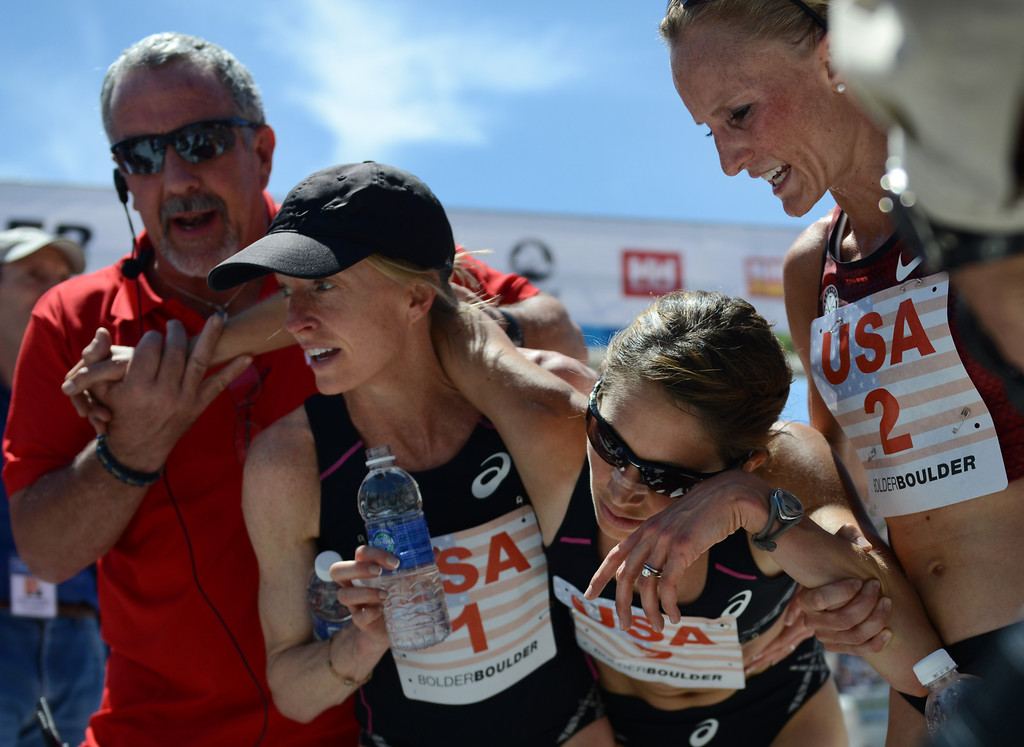 . A race official, far left, Deena Kastor, (1) and Shalane Flanagan (2), right, help U.S.A. teammate Sara Hall stay on her feet after she crossed the finish line in the women\'s international team competition of the 36th Annual BolderBOULDER 10K road race on Memorial Day, May 26, 2014.  (Photo By Lindsay Pierce/The Denver Post)