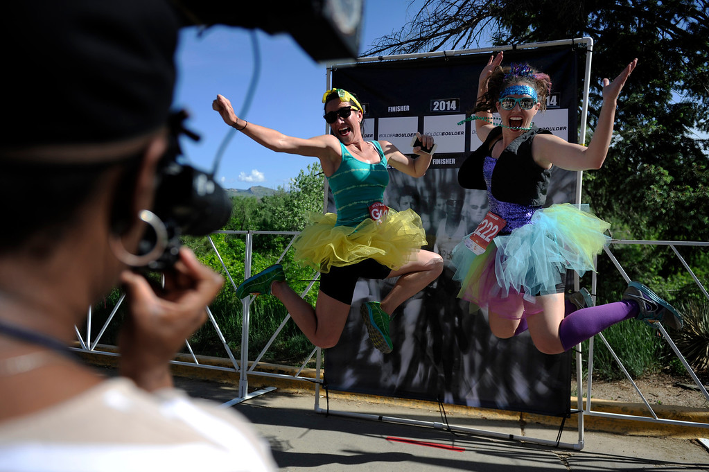 . Stasia Raines, left, and Cristianna Rupple, of Denver, jump for the race photographer after completing the 36th Annual Bolder Boulder 10K road race on Memorial Day, May 26, 2014. (Photo By Lindsay Pierce/The Denver Post)
