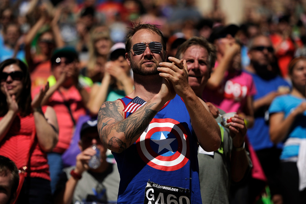 . Fans stand up to cheer as a group of service members cross the finish line during the 36th Annual Bolder Boulder 10K road race on Memorial Day, May 26, 2014. (Photo By Lindsay Pierce/The Denver Post)