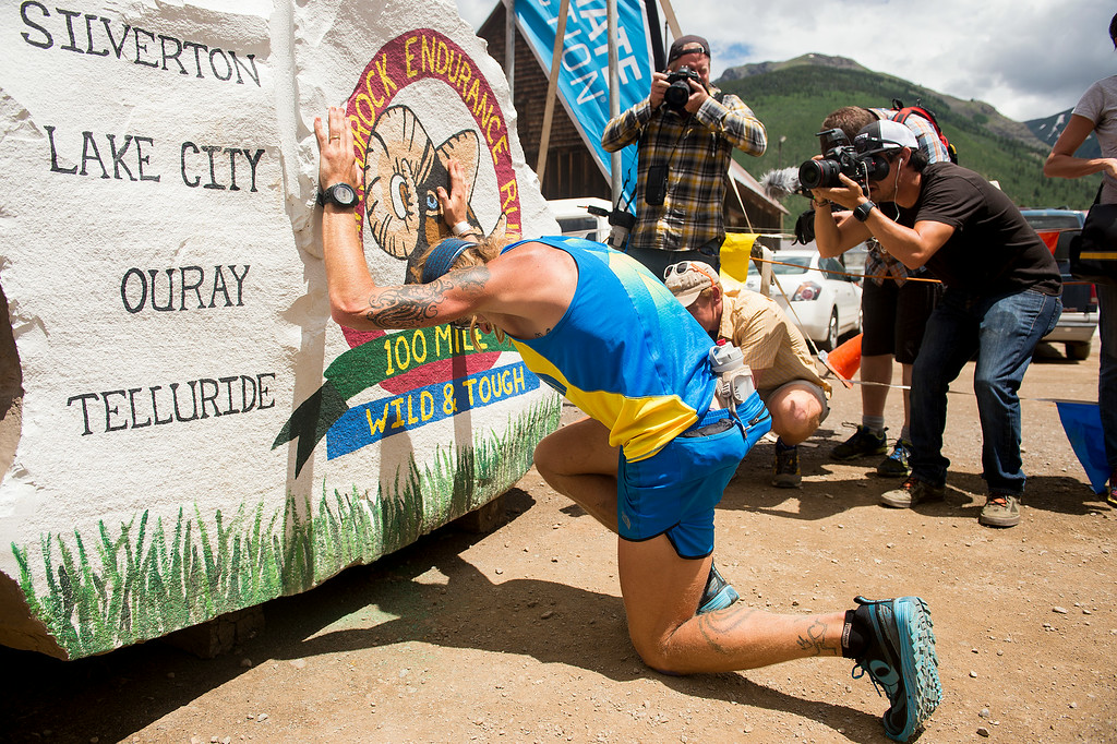 . SILVERTON, CO - JULY 12: Timothy Olson kneels in front of the hard rock before kissing it to signal the end of the 100.5-mile Hardrock 100 Endurance Run on July 12, 2014, in the San Juan Mountains, Colorado. Olson, a top competitor in the race, finished 12th after suffering stomach issues for more than half the race and being unable to hold down food or drink. (Photo by Daniel Petty/The Denver Post)