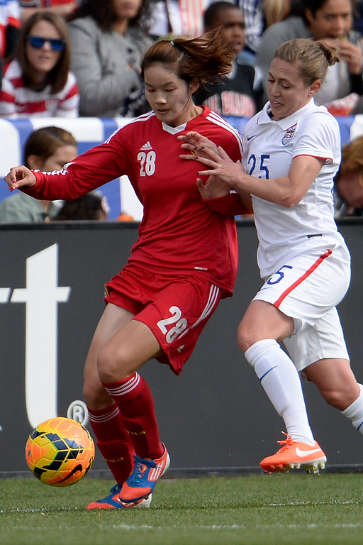 . Megan Klingenberg (25) of the U.S.A. defends Zhang Xin of China during the first half of women\'s soccer action. Dick\'s Sporting Goods Park on Sunday, April 6, 2014. (Photo by AAron Ontiveroz/The Denver Post)