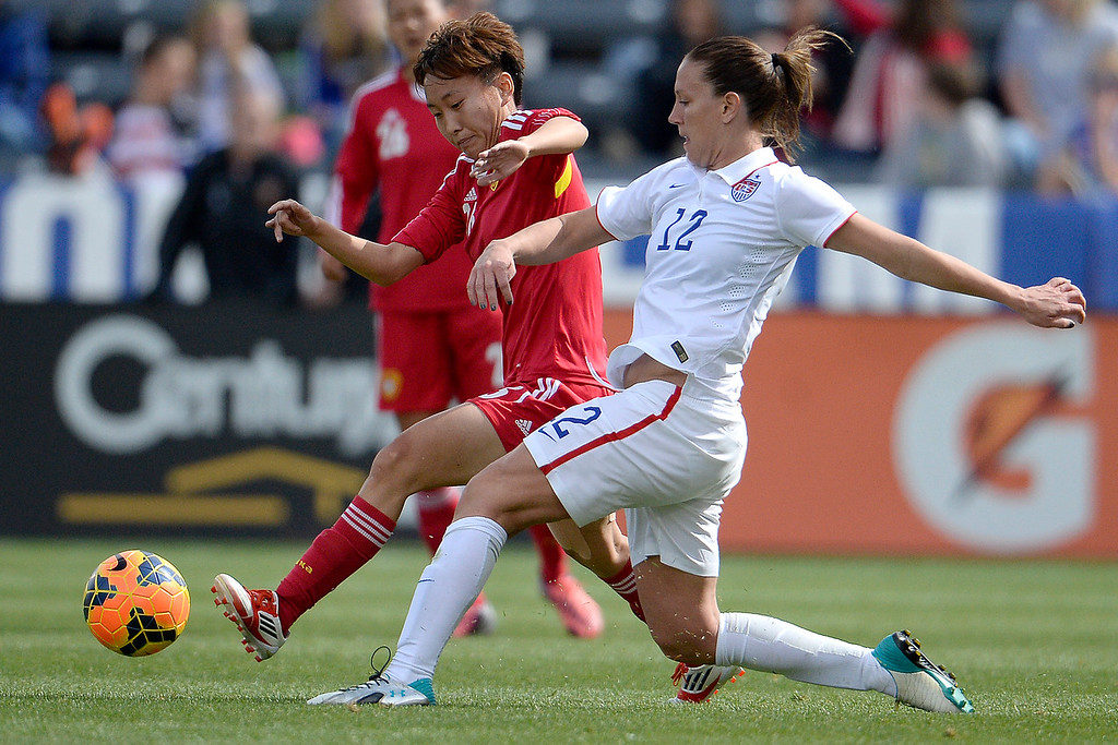 . Li Dongna (26) of China and Lauren Holiday (12) of the U.S.A. race for the ball during the first half of women\'s soccer action. Dick\'s Sporting Goods Park on Sunday, April 6, 2014. (Photo by AAron Ontiveroz/The Denver Post)