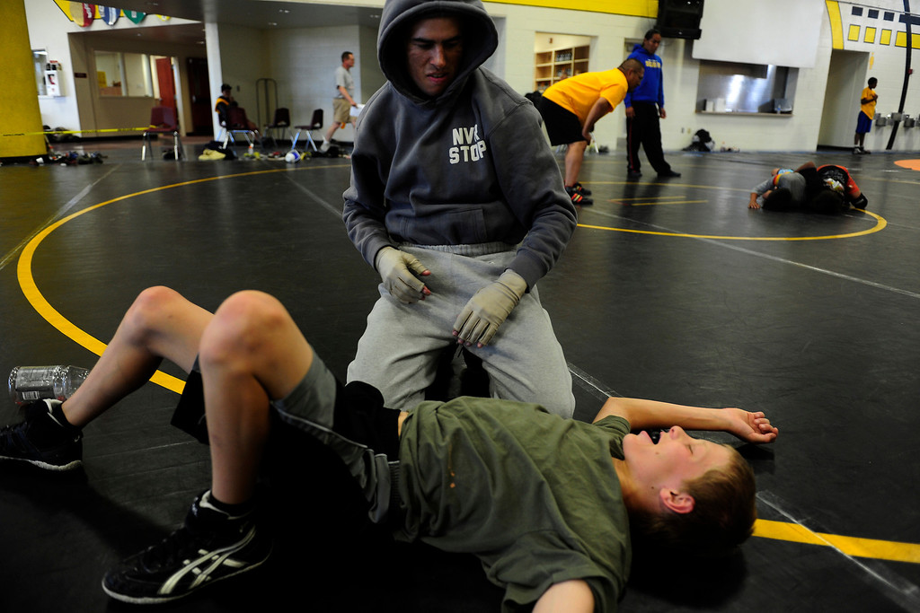 . PAGOSA SPRINGS, CO. - JUNE 6: Michael Martinez talks about moves with Trevor Bryant 14, a wrestler for Pagosa Springs High School on June 6, 2013 at the Wrestle the World wrestling camp. He admits he shouldn\'t be scrapping with kids yet because it could break his skin, but does it anyway. Martinez, 27, two-time state wrestling champion at Pagosa Springs High School and three-time Western Wrestling Conference champion at Wyoming, survived a propane explosion on April 2, 2013, that blew up a camper on his parents ranch. Eighty percent of his body was covered in 2nd and 3rd degree burns. (Photo By Mahala Gaylord/The Denver Post)