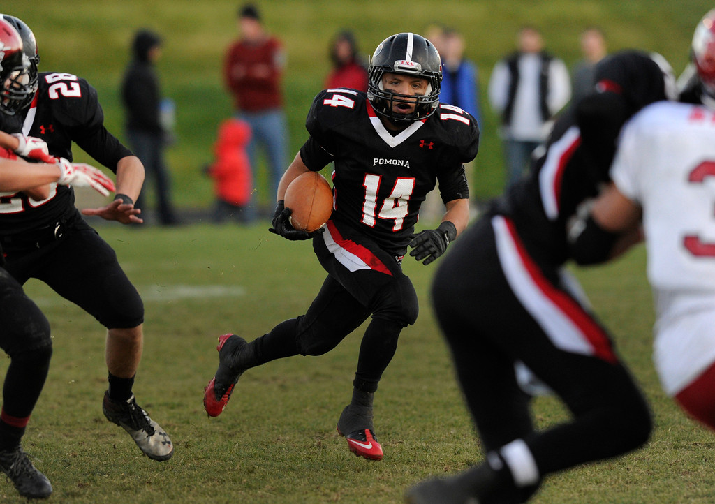. ARVADA, CO. - OCTOBER 18: Pomona senior running back Chris Marquez (14) looked for room to run in the fourth quarter. The Fairview High School football team remained undefeated with a 33-30 win over Pomona Friday night, October 18, 2013. The Knights kicked a field goal as time expired in the fourth quarter. Photo By Karl Gehring/The Denver Post