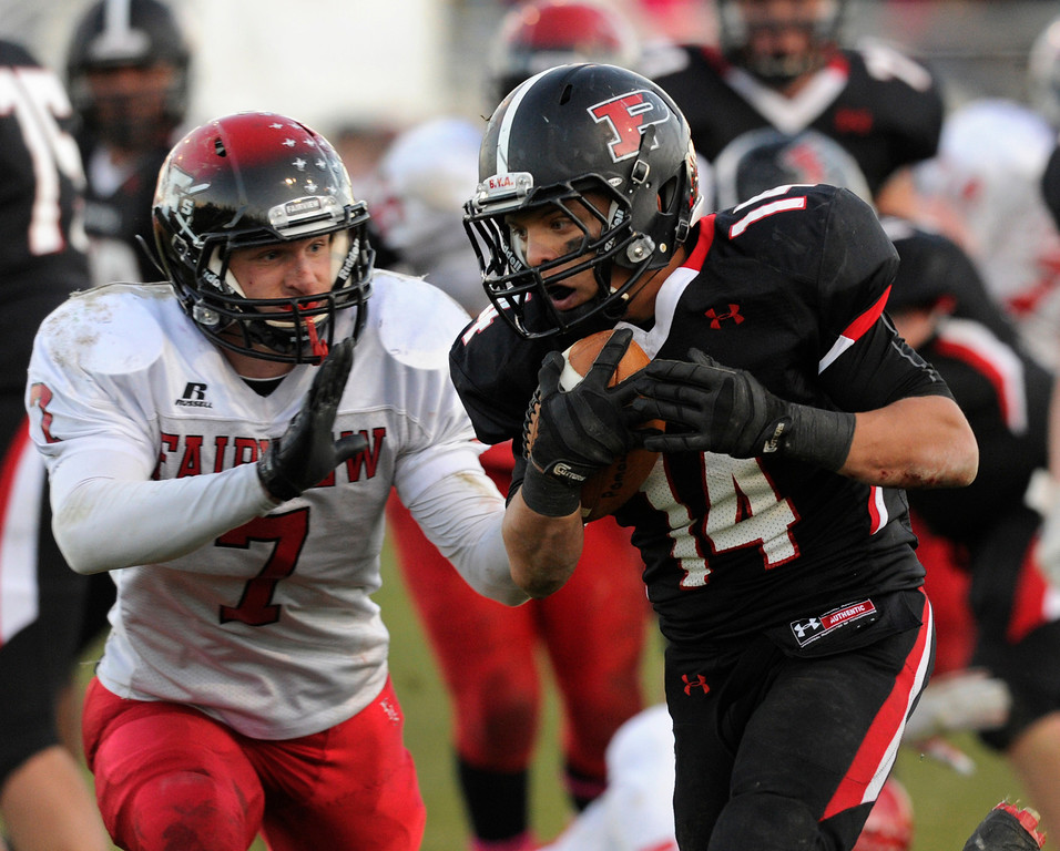 . ARVADA, CO. - OCTOBER 18: Pomona senior running back Chris Marquez (14) slipped past Fairview defender Jonathan Swartzwelter (14) for a fourth quarter touchdown. The Fairview High School football team remained undefeated with a 33-30 win over Pomona Friday night, October 18, 2013. The Knights kicked a field goal as time expired in the fourth quarter. Photo By Karl Gehring/The Denver Post