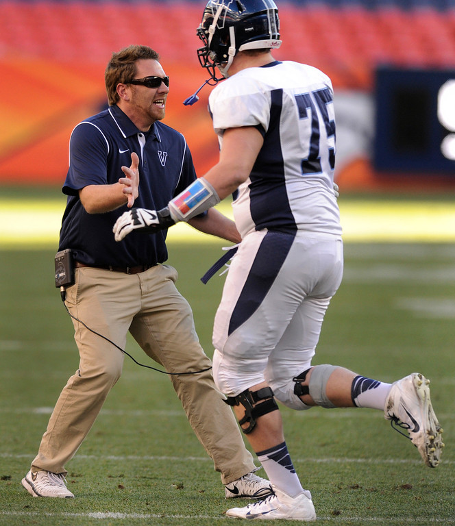 . Eagles\' coach Rod Sherman congratulated senior lineman Alec Ruth (75) after a touchdown scoring drive in the first half. The Valor Christian football team took on Fairview in the 5A championship game Saturday, November 30, 2013. Photo By Karl Gehring/The Denver Post