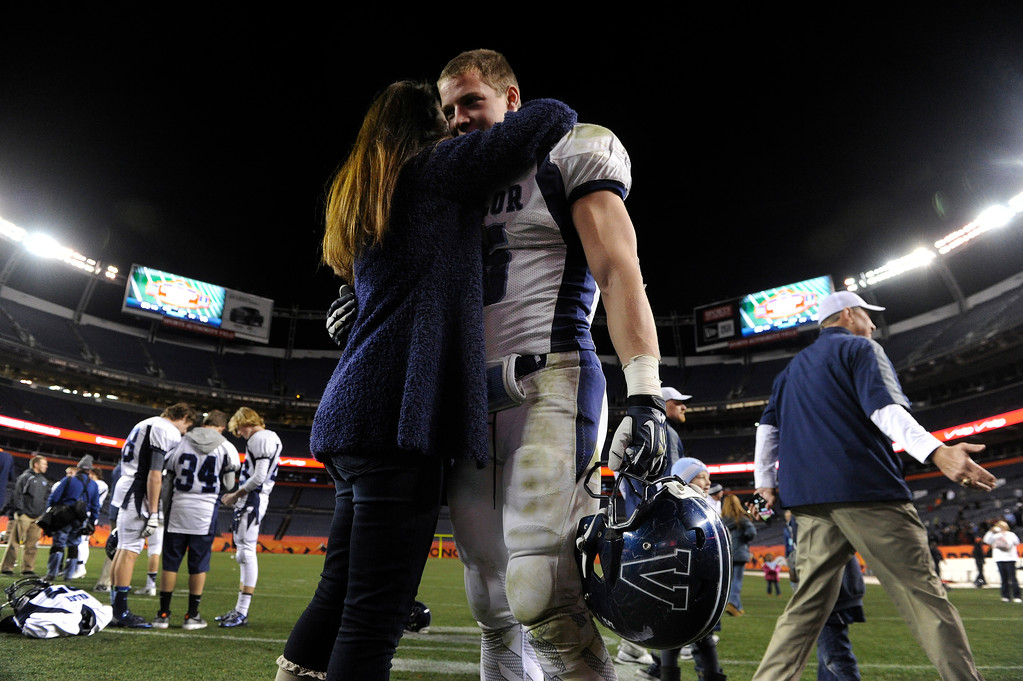 . Eagles\' running back Christian McCaffrey got a hug and kiss from his mother Lisa after the game. The Valor Christian football team rolled past Fairview 56-16 in the 5A championship game Saturday, November 30, 2013. Photo By Karl Gehring/The Denver Post