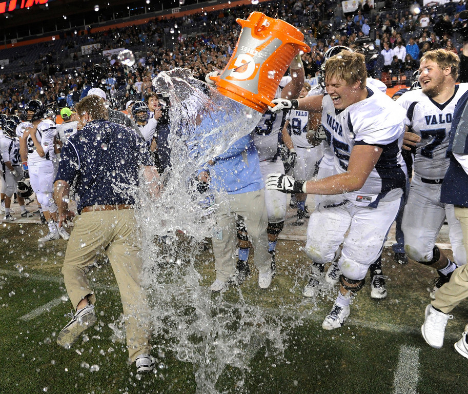 . Eagles\' coach Rod Sherman did his best to avoid a bucket of ice water his players wanted to dump over him at the end of the game. The Valor Christian football team rolled past Fairview 56-16 in the 5A championship game Saturday, November 30, 2013. Photo By Karl Gehring/The Denver Post