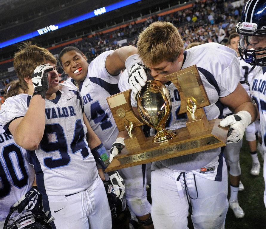 . Eagles\' offensive lineman Alec Ruth (75) kissed the championship trophy at midfield following the win. The Valor Christian football team rolled past Fairview 56-16 in the 5A championship game Saturday, November 30, 2013. Photo By Karl Gehring/The Denver Post
