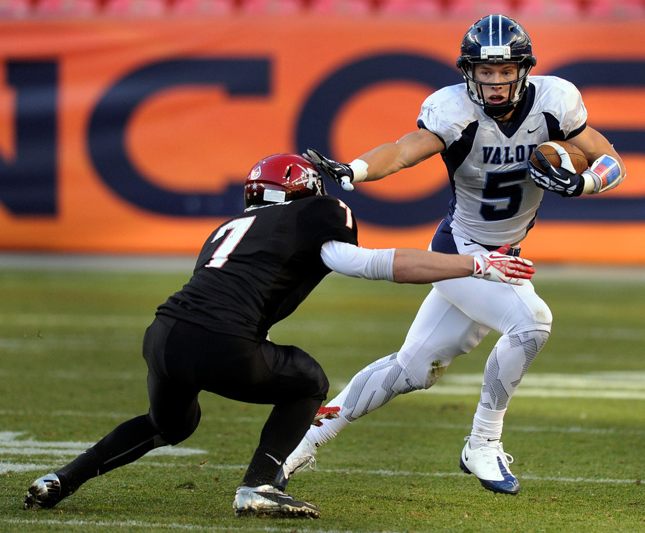 . Eagles\' running back Christian McCaffrey (5) used a straight-arm move to try to get past Fairview defender Jonathan Schwartwelter (7) on a run in the first half. The Valor Christian football team took on Fairview in the 5A championship game Saturday, November 30, 2013. Photo By Karl Gehring/The Denver Post