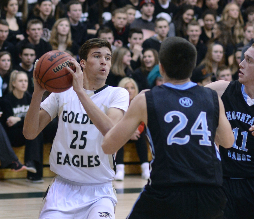 . Golden Eagles\' senior forward Graham Smith (25) looked for a way past Mountain Range defenders James Potter (24) and Logan Tanner (11) in the fourth quarter. The Mountain Vista boy\'s basketball team defeated Mountain Range 78-56 Saturday night, March 1, 2014. Photo By Karl Gehring/The Denver Post