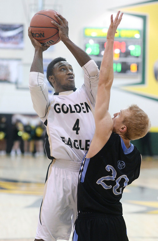 . Golden Eagles\' guard Jonathan Moore (4) put up a shot over Mustangs\' defender Ben Egan (20) in the first half. The Mountain Vista boy\'s basketball team defeated Mountain Range 78-56 Saturday night, March 1, 2014. Photo By Karl Gehring/The Denver Post