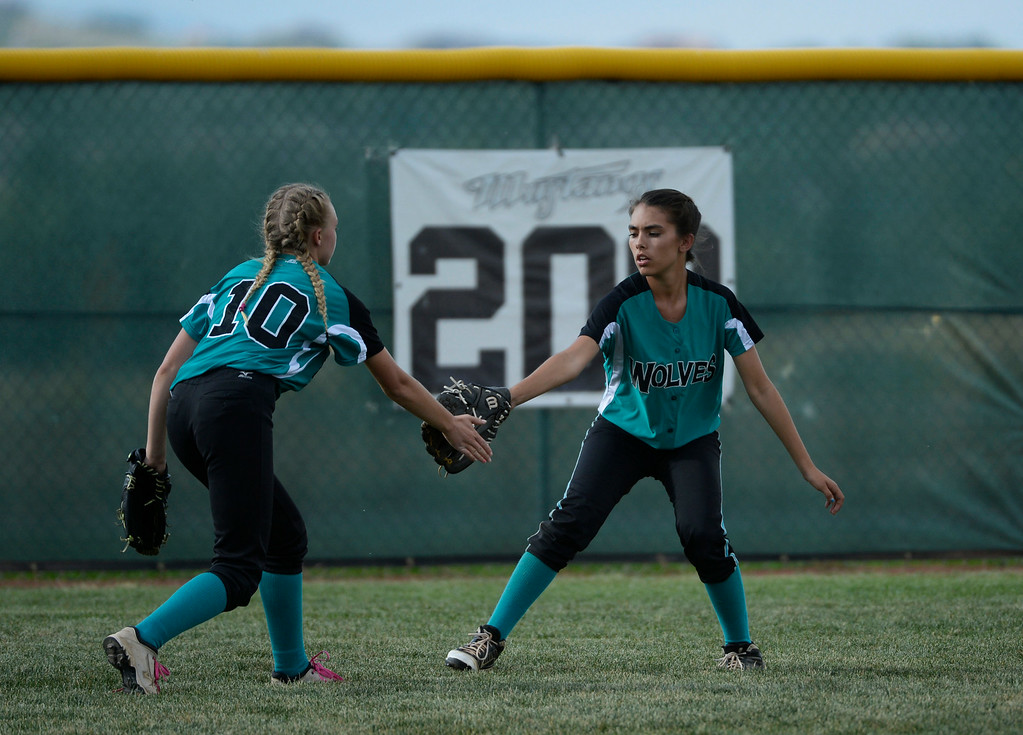 . Westminster High School outfielder, Angel Micciulli, right, gets support from fellow outfielder, Natalie Taylor, left, after Micciulli made a catch for an out against Mountain Range High School during the championship game of the inaugural 2014 King of the Mountain 5A softball tournament at Mountain Range High School Saturday afternoon, August 30, 2014. (Photo By Andy Cross / The Denver Post)