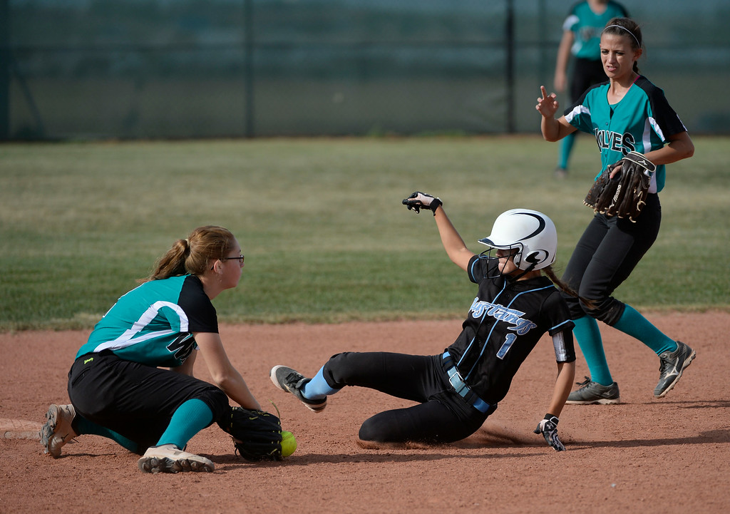 . Mountain Range High School softball player, Kaylee Dethouars, beats the throw and tag on a steal at second base in the 5th inning against Westminster infielders, Kristin Doell, left, and Nicole Taylor, right, during the championship game of the inaugural 2014 King of the Mountain 5A softball tournament at Mountain Range High School Saturday afternoon, August 30, 2014. (Photo By Andy Cross / The Denver Post)