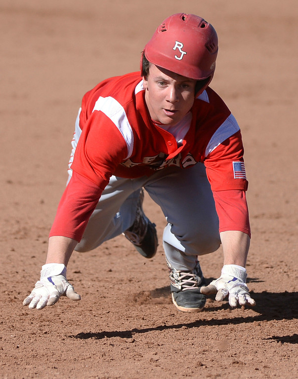 . Raiders baserunner Max George hustled to third base after an attempt to pick him off first-base failed in the second inning. The Regis Jesuit baseball team defeated Rock Canyon 10-1 Friday afternoon, April 11, 2014.  (Photo by Karl Gehring/The Denver Post)