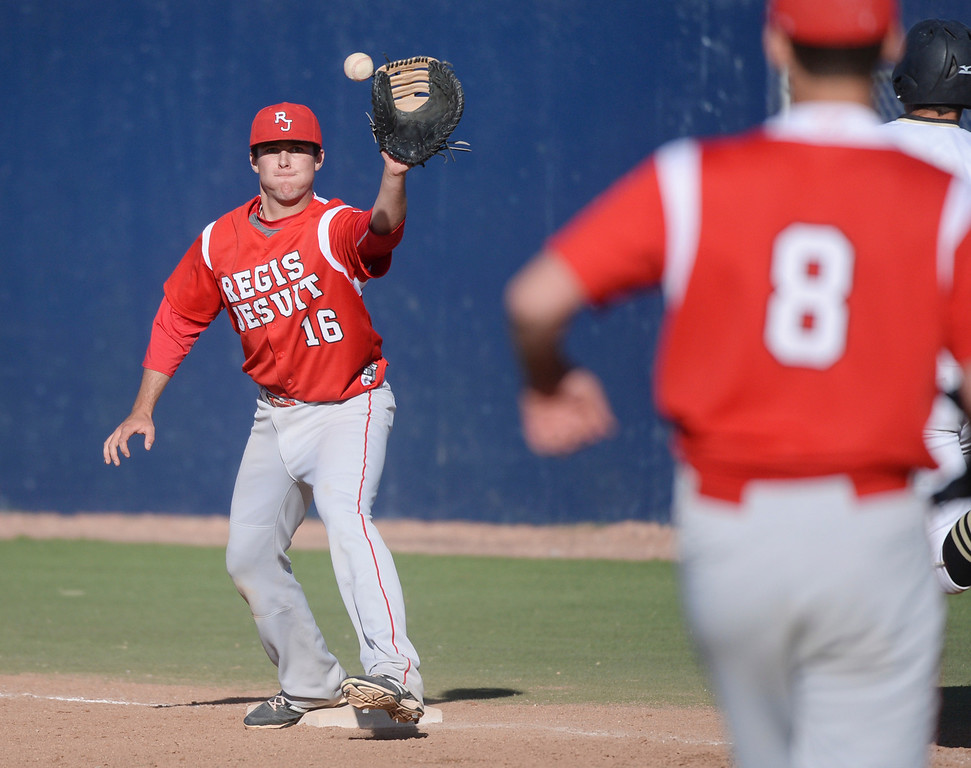 . Regis infielder fielded the throw at first base to retire Rock Canyon batter Ben Sneider in the fourth inning. The Regis Jesuit baseball team defeated Rock Canyon 10-1 Friday afternoon, April 11, 2014.  (Photo by Karl Gehring/The Denver Post)