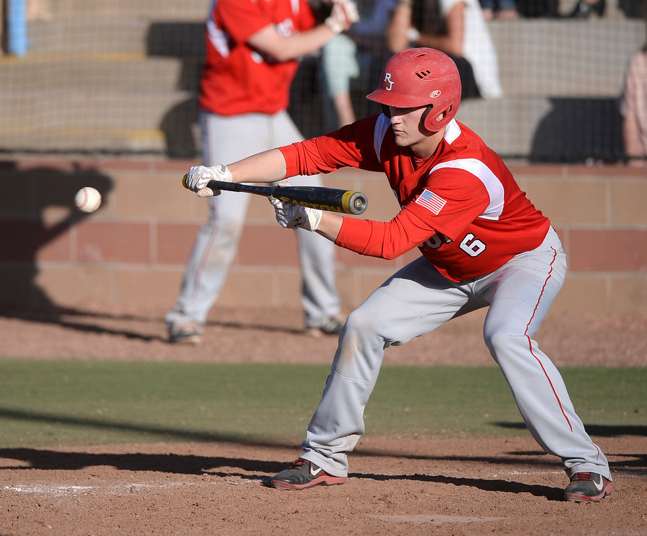 . Regis batter Zach Woodruff put down a bunt to advance base runners in the sixth inning. The Regis Jesuit baseball team defeated Rock Canyon 10-1 Friday afternoon, April 11, 2014.  (Photo by Karl Gehring/The Denver Post)