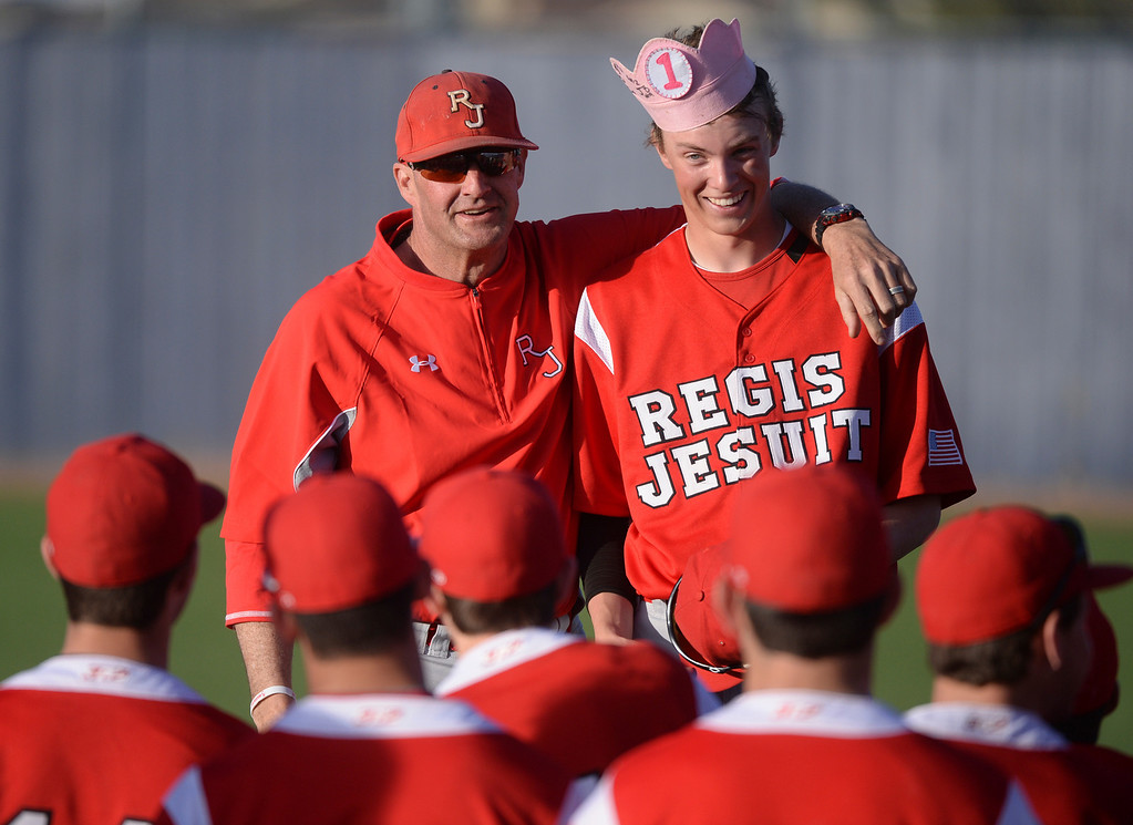 . Raiders coach Matt Darr presented junior Aidan Cameron with a gag batting crown after a sixth-inning grand slam home run broke the game open Friday. The Regis Jesuit baseball team defeated Rock Canyon 10-1 Friday afternoon, April 11, 2014.  (Photo by Karl Gehring/The Denver Post)