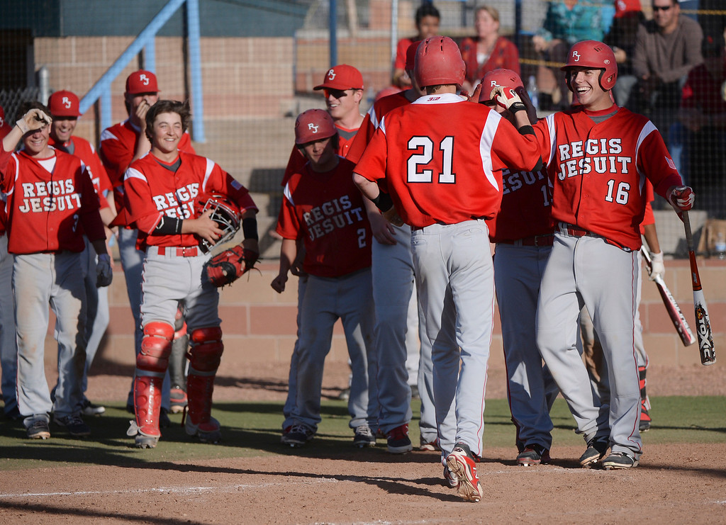 . Raiders\' teammates met  junior Aidan Cameron at home plate after he blasted a sixth-inning grand slam home run over the right field fence. The Regis Jesuit baseball team defeated Rock Canyon 10-1 Friday afternoon, April 11, 2014.  (Photo by Karl Gehring/The Denver Post)