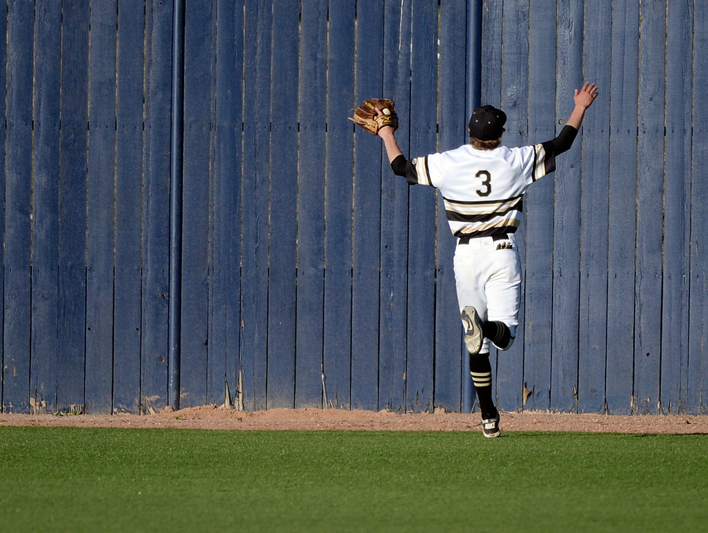 . Rock Canyon outfielder Danny Costello ran out of room after Regis batter Aidan Cameron blasted a sixth-inning grand slam home run over the right field fence. The Regis Jesuit baseball team defeated Rock Canyon 10-1 Friday afternoon, April 11, 2014.  (Photo by Karl Gehring/The Denver Post)