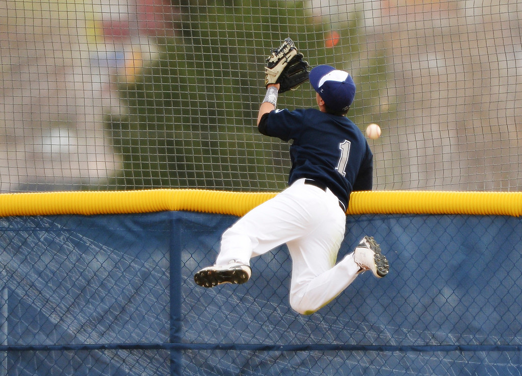 . Adrian Trujillo of Columbine High School (1) tries to catch a home-run ball hit by Jacob Falbo of Chatfield.   (Photo by Hyoung Chang/The Denver Post)