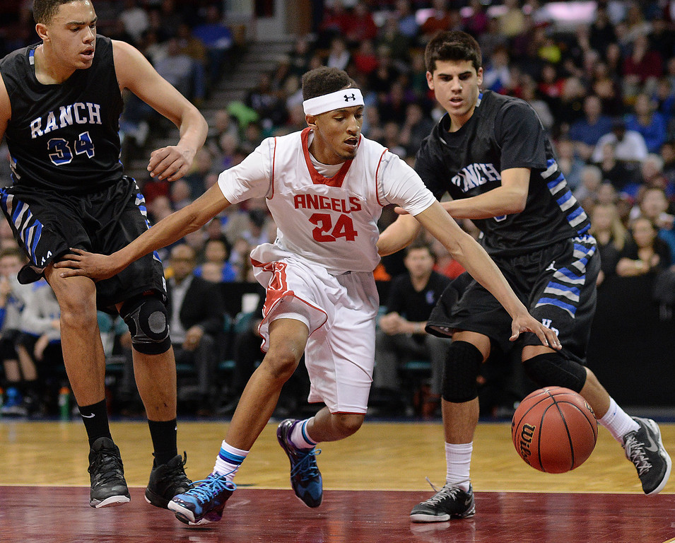 . DENVER, CO - MARCH 7: East guard Dom Collier dribbled through the lane in the first half. The Denver East High School boy\'s basketball team defeated Highlands Ranch 64-44 in a 5A quarterfinal playoff game Friday night, March 7, 2014 in Denver, Colorado. (Photo by Karl Gehring/The Denver Post)