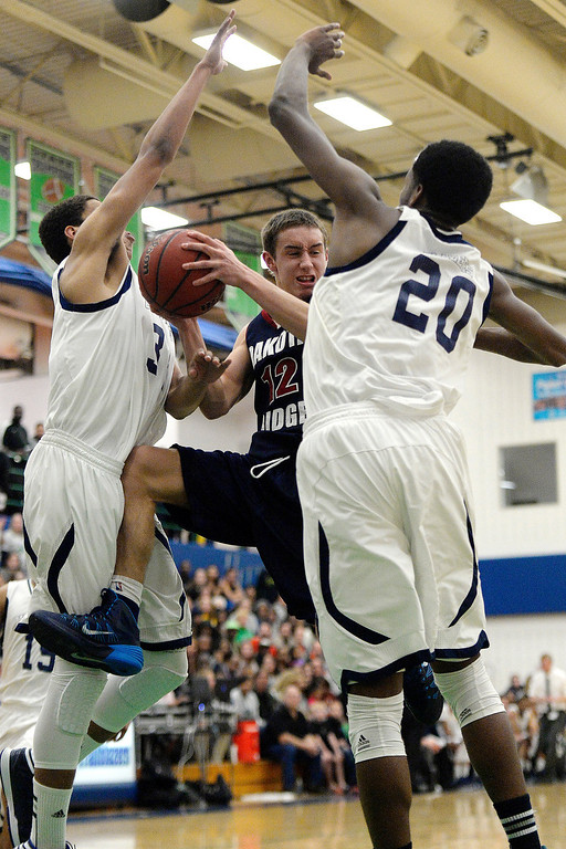 . Jake Flores (12) of the Dakota Ridge Eagles gets mobbed by Ryan Swan (34) of the Overland Trailblazers and De�Ron Davis (20) during the second half. (Photo By AAron Ontiveroz/The Denver Post)